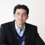Headshot of Dr Manolis Kellis, a white man with black hair and blue eyes