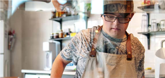 A young man with Down syndrome works in a cafe