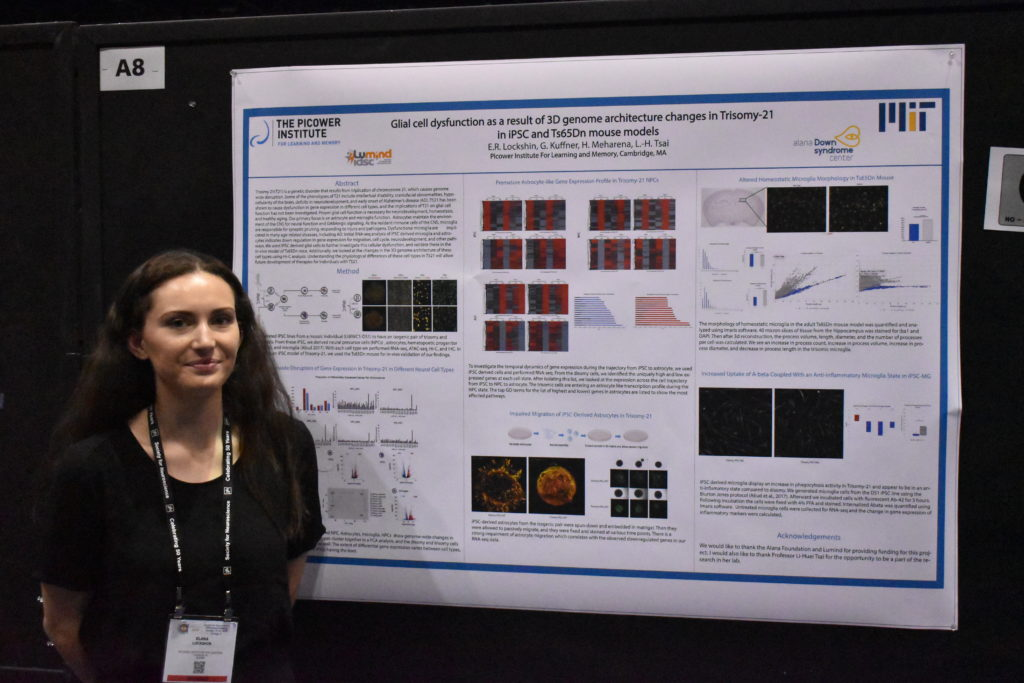 A woman stands with a research poster at a neuroscience conference