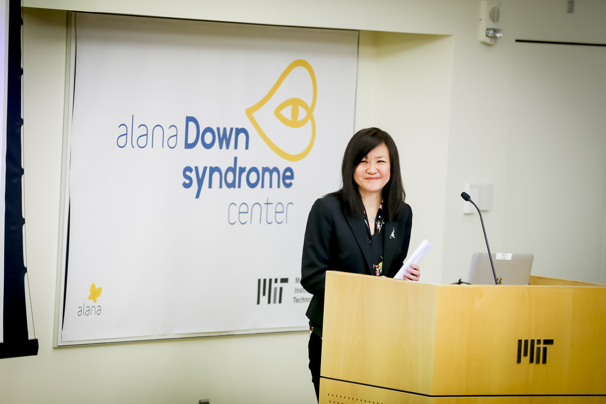 Li-Huei Tsai stands at an MIT podium with the Alana Center logo in the background